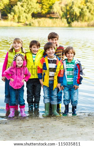 Cute kids group in rubber boots - stock photo