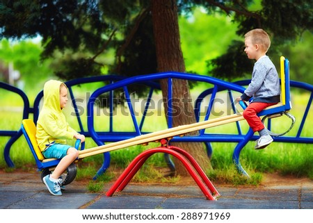 cute kids having fun on seesaw at playground - stock photo
