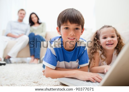 Cute kids playing computer games on laptop together - stock photo