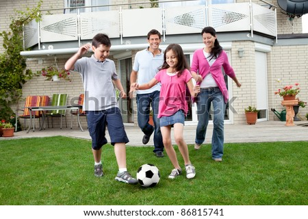 Cute kids playing football with their parents at backyard - stock photo