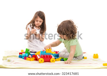 Cute kids playing home with colorful cubes toys against white background