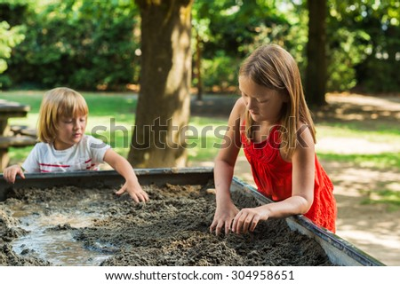 Cute kids playing in a sandbox - stock photo