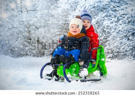Cute kids playing outdoors in winter - stock photo