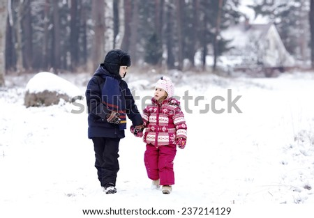 cute kids playing outdoors in winter time, brother and sister