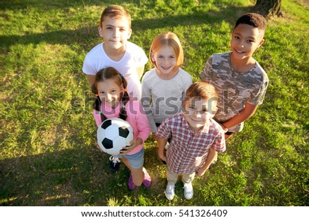 Cute kids playing with ball on green grass