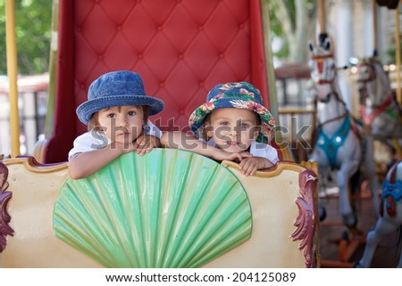 Cute kids, riding on a carousel in Europe - stock photo