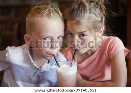 Cute kids sharing a mint Italian soda drink at a cafe - stock photo