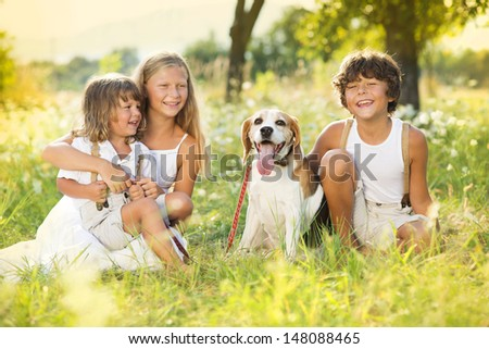Cute kids spending time outside with their dog - stock photo