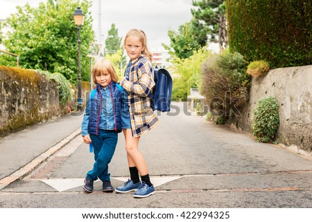 Cute kids with backpacks walking to school - stock photo