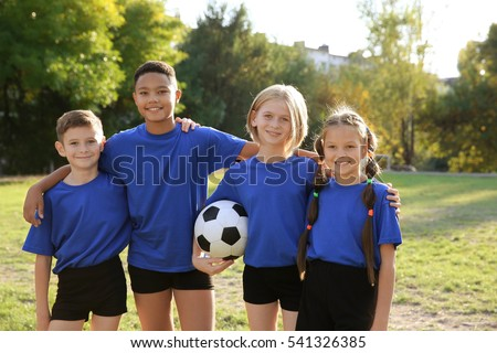 Cute kids with football ball on field