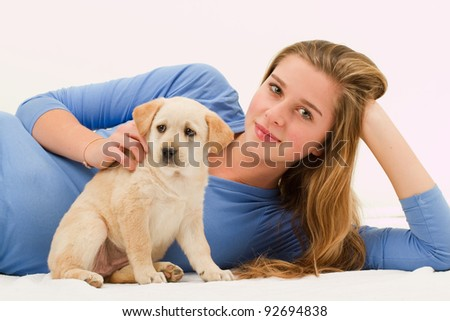 Cute Labrador puppy and happy young girl - portrait of young female with her pet dog