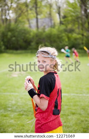 cute lacrosse player on the sideline of the game - stock photo