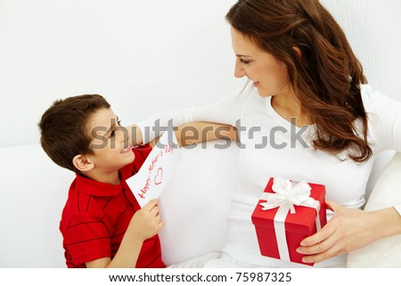 Cute lad with congratulating card looking at his mother with giftbox - stock photo