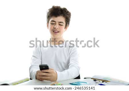 Cute Latin boy  with soft and smooth skin wearing a white long sleeve t-shirt smiles using his cell phone, a smartphone, on homework - stock photo
