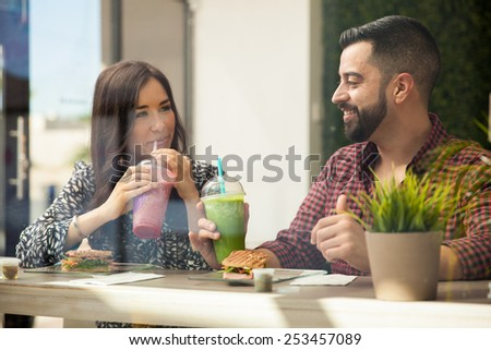 Cute Latin couple drinking smoothies and eating sandwiches during a date - stock photo