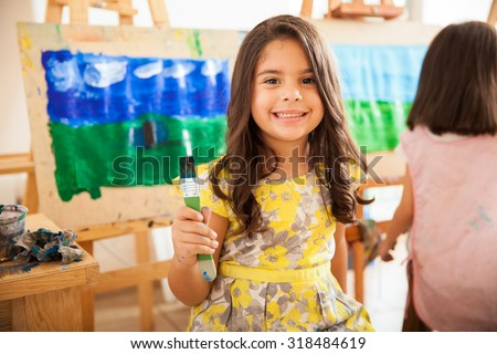 Cute Latin girl holding a paintbrush and smiling during art class at school - stock photo