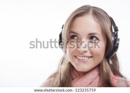 Cute latin woman listening to music and looking towards copy space - stock photo