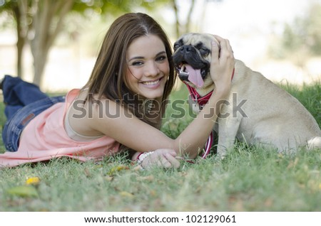 Cute latin woman spending some time with her pug dog at the park - stock photo