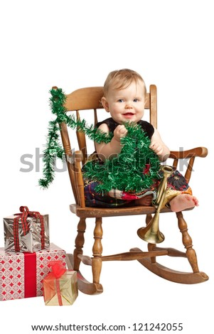 Cute laughing baby in velvet embroidered patchwork dress sits in rocking chair with festive holiday gifts and garland. Vertical, isolated/cut out on white background, copy space.