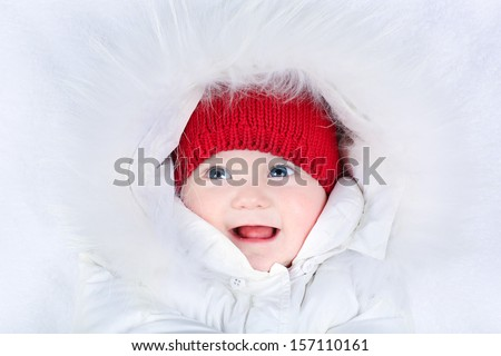 Cute laughing baby with beautiful blue eyes in a white snow suit and a warm red knitted hat - stock photo