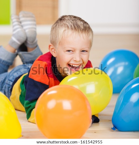 Cute laughing birthday boy lying on the floor amongst brightly colored party balloons - stock photo