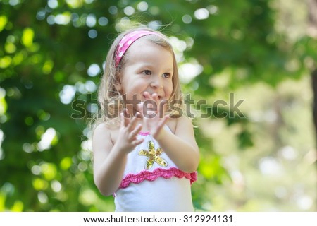 Cute laughing blonde toddler girl is clapping with her palms  - stock photo