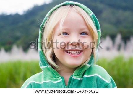 Cute laughing child in a green hoodie, standing in a sugar cane field - stock photo
