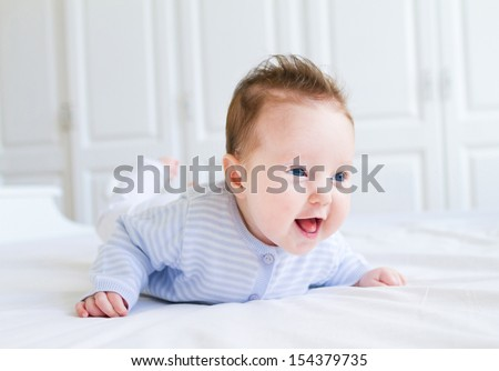 Cute laughing little baby enjoying her tummy time on a white blanket wearing a knitted blue sweater