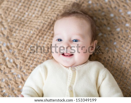 Cute laughing little baby in a warm sweater on a brown knitted blanket - stock photo