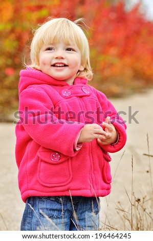 cute laughing toddler girl in fall park - stock photo