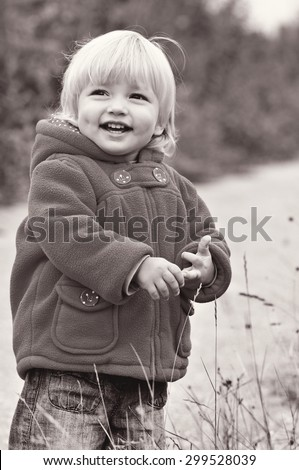 cute laughing toddler girl in fall park