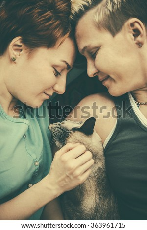 Cute lesbian couple cuddle their pet. Toned picture - stock photo