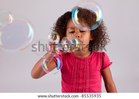 Cute little African American girl blowing soap bubbles - stock photo