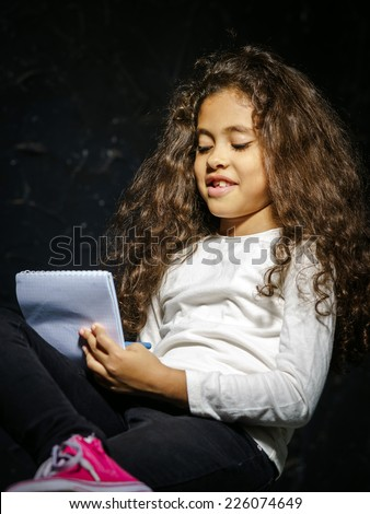 Cute little african-american girl painting on black background - stock photo