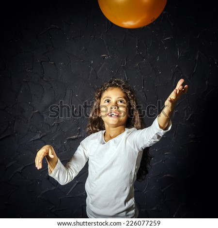 Cute little african-american girl plaing with orange balloon - stock photo