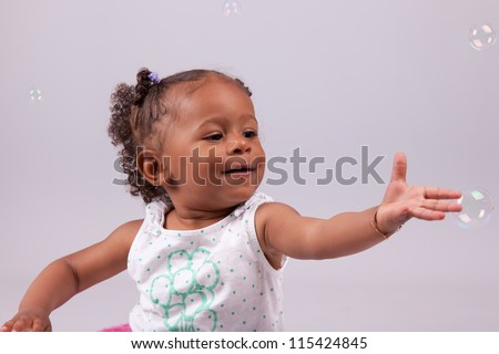 Cute little African American girl playing with soap bubbles - stock photo