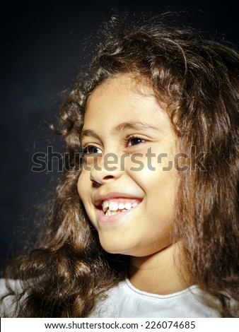 Cute little african-american girl portrait on black background
