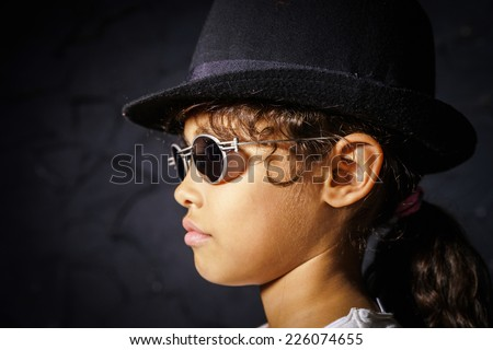 Cute little african-american girl with sunglasses like Michael Jackson - stock photo