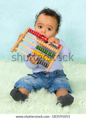 Cute little African baby boy playing with an abacus - stock photo