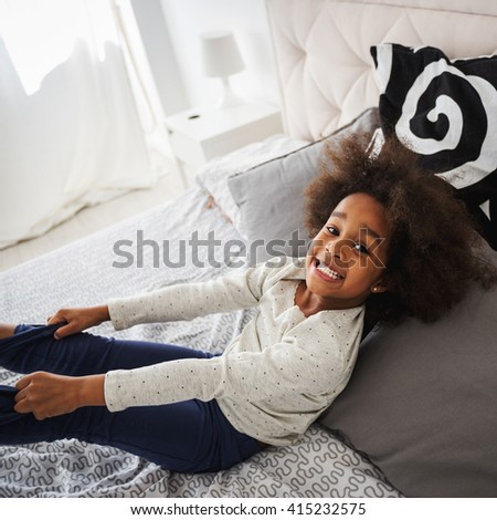 Cute little african girl having fun in bed. - stock photo