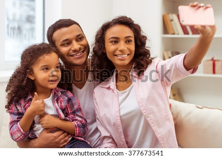Cute little Afro-American girl and her beautiful young parents hugging and smiling while sitting on a sofa in the room. Mother making a photo. - stock photo