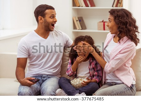Cute little Afro-American girl and her beautiful young parents sitting on a sofa and watching TV. - stock photo