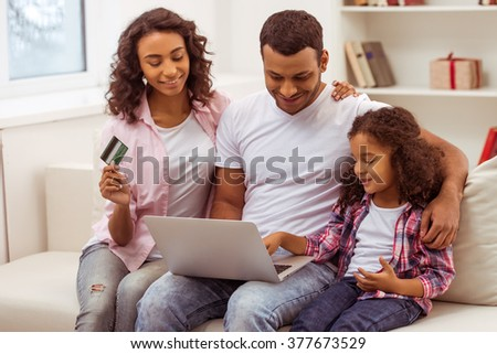 Cute little Afro-American girl and her beautiful young parents using a laptop and doing shopping online while sitting on a sofa at home. Mother holding a credit card. - stock photo