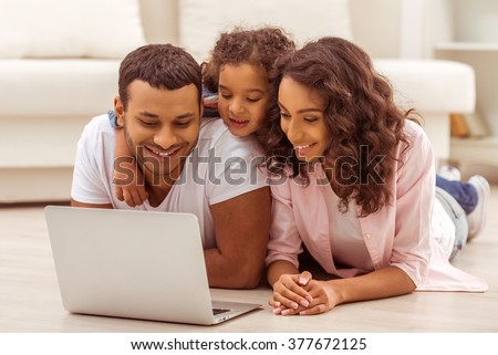 Cute little Afro-American girl and her beautiful young parents using a laptop and smiling while lying on the floor in the room. - stock photo