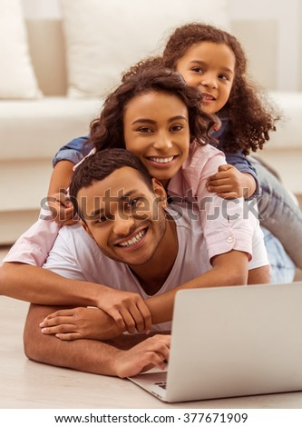 Cute little Afro-American girl and her beautiful young parents using a laptop, hugging, looking at camera and smiling while lying on the floor in the room.
