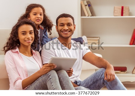 Cute little Afro-American girl and her beautiful young parents using a tablet, looking at camera and smiling while sitting in the room. - stock photo