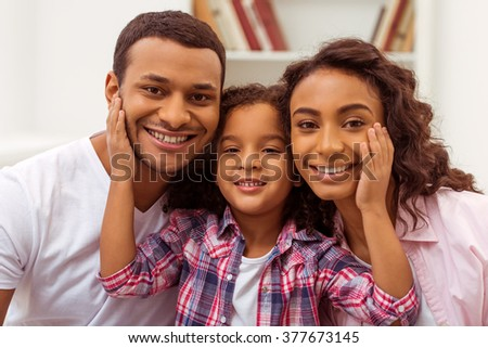 Cute little Afro-American girl hugging her beautiful young parents. All looking at camera and smiling. - stock photo