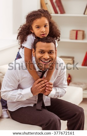 Cute little Afro-American girl hugging her handsome young father. Both looking at camera and smiling. - stock photo
