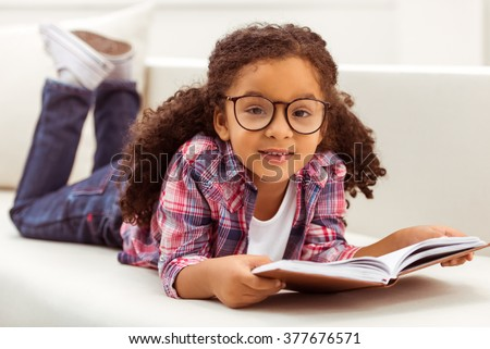 Cute little Afro-American girl in casual clothes and eyeglasses reading a book, looking at camera and smiling while lying on a sofa in the room. - stock photo