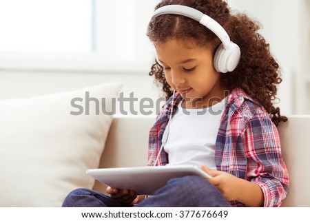 Cute little Afro-American girl in casual clothes and headphones using a tablet and listening to music while sitting on a sofa in the room. - stock photo